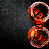 Two glasses of brandy on black stone background, top view