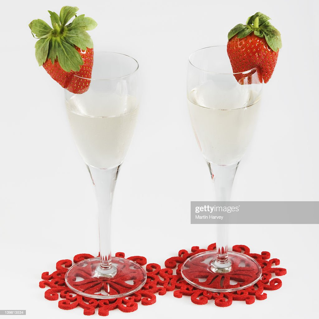 Two glasses of champagne with whole strawberries decorating rim, glasses placed on coaster, against white background : Stock Photo
