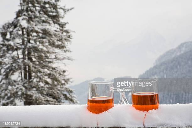 Two glasses of drink sit on a snow covered ledge