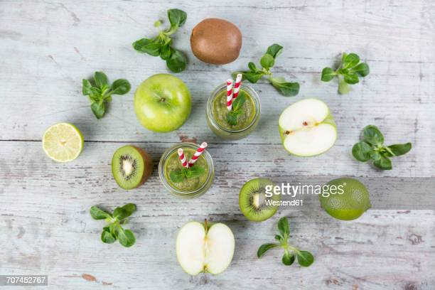 Two glasses of green smoothie and ingredients on wood