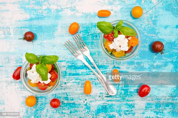 Two glasses of leaf salad with goat cream cheese and tomatoes