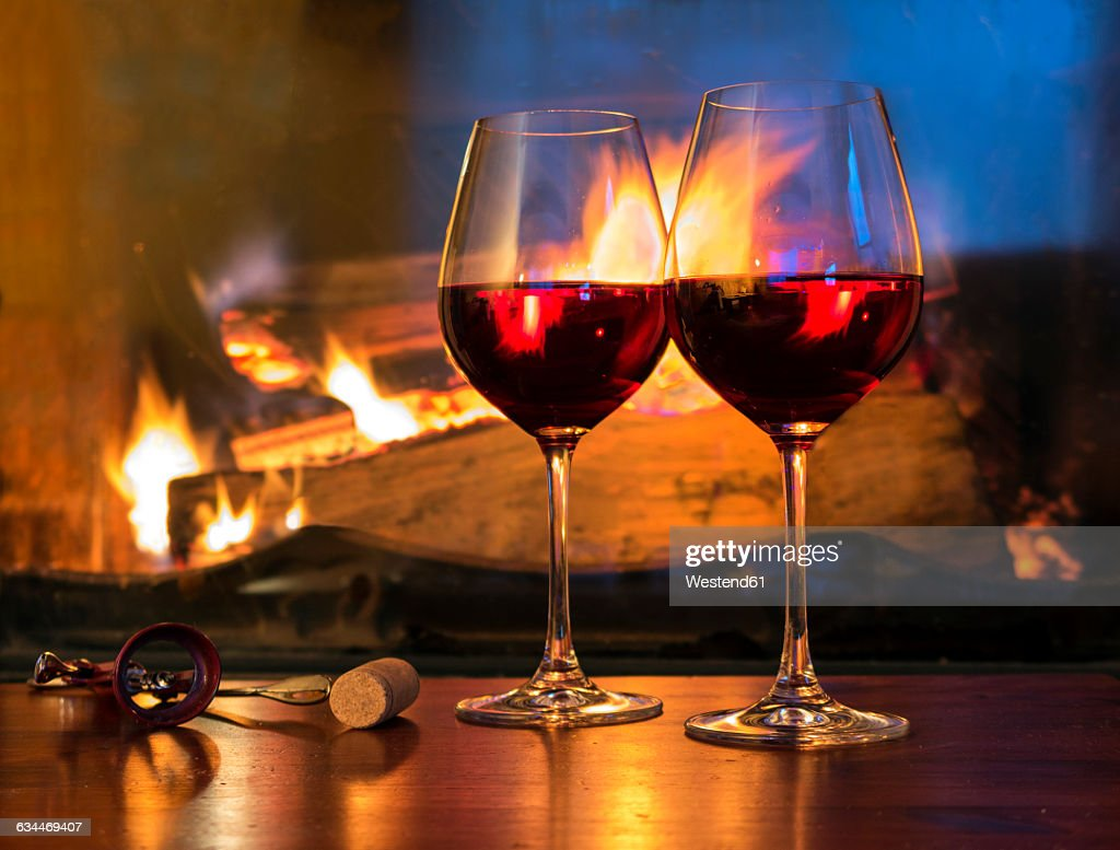 two glasses of red wine in front of a fireplace stock photo