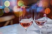 Closeup of pair of wine glasses against de focused background
