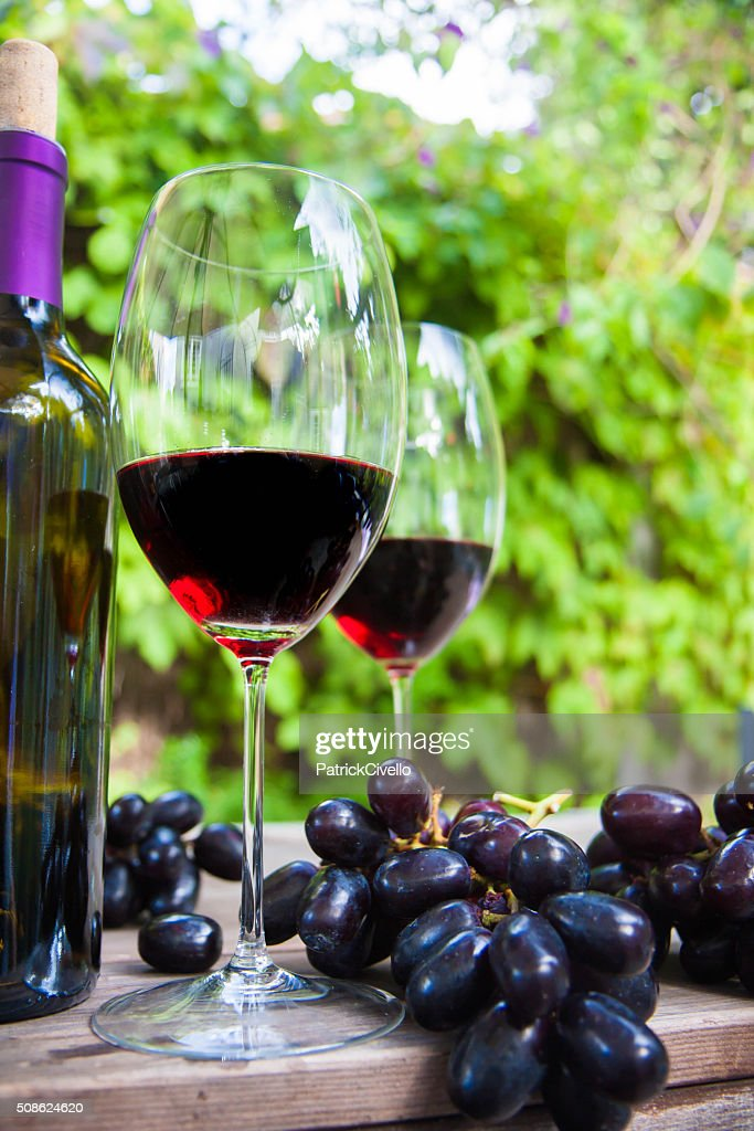 Two glasses of red wine with bottle and grapes : Stock Photo