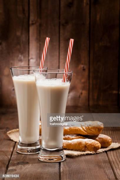 Dos vasos de refrescante bebida de Horchata de chufa y fartons en la rústica mesa de madera