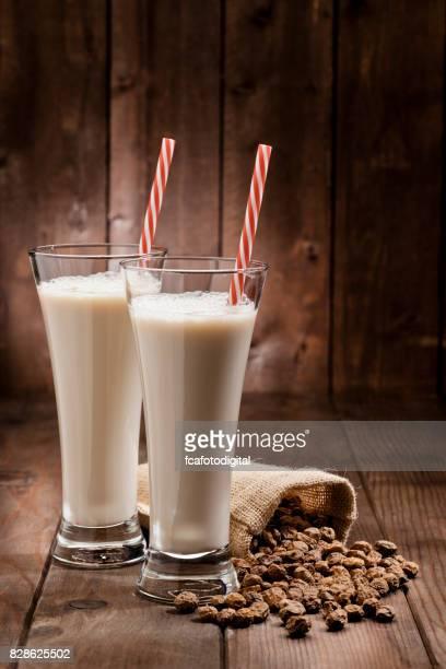 Dos vasos de refrescante Horchata de Chufa beben tiro en mesa de madera rústica