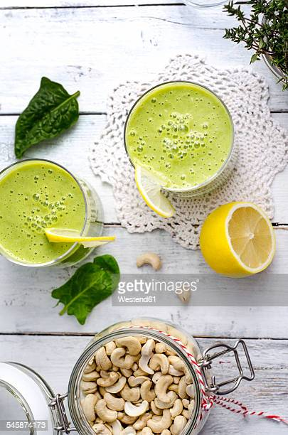 Two glasses of spinach smoothie, cashew nuts and half of a lemon on wood