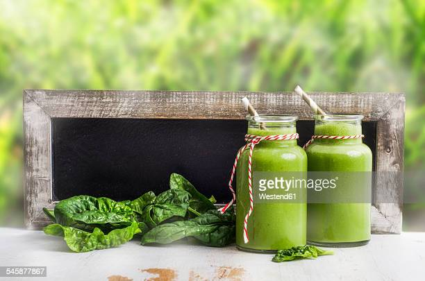 Two glasses of spinach smoothie, spinach leaves and blackboard