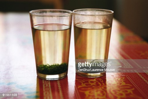 Two glasses of tea with tea leaves steeping : Stock Photo