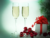 two glasses with champagne, and boxes with gifts on Christmas background .photo with copy space.