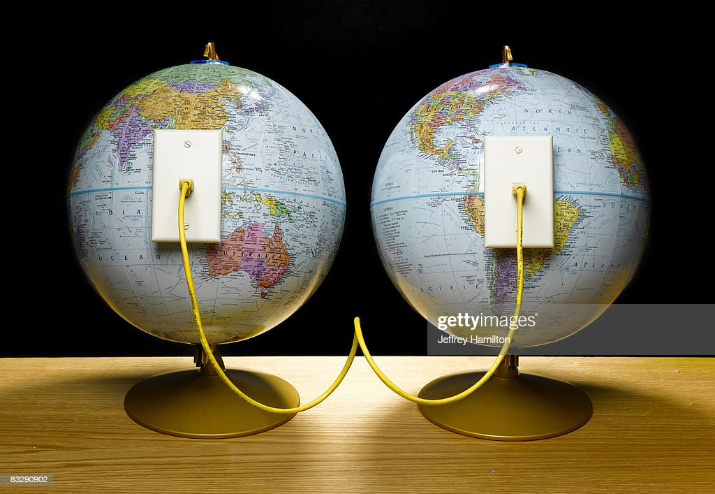 Two globes connected by ethernet cable : Stock Photo