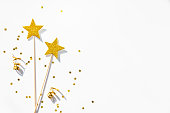 Two golden party magic wands, sequins and ribbons on a white background. Copy space.