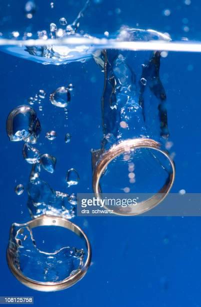 Zwei goldene Hochzeit Ringe sinken im Wasser