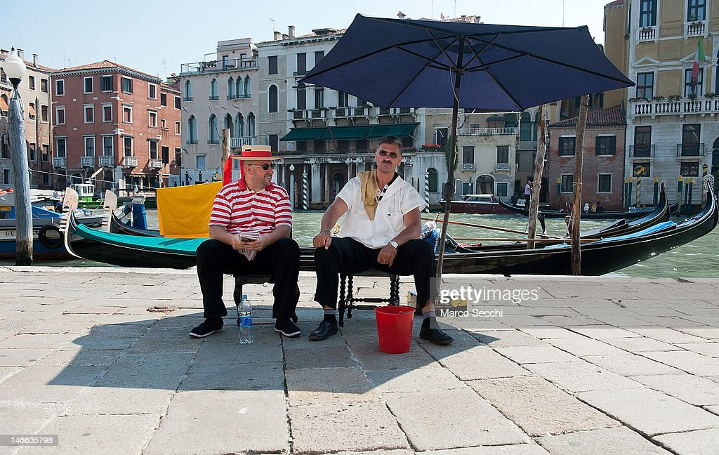 Two gondoliers sit under a large umbrella on the bank of the Grand Canal on June 21, 2012 in Venice, Italy. An intense heatwave is sweeping across many regions in Italy, prompting the country's health ministry to issue a number of high level alerts.
