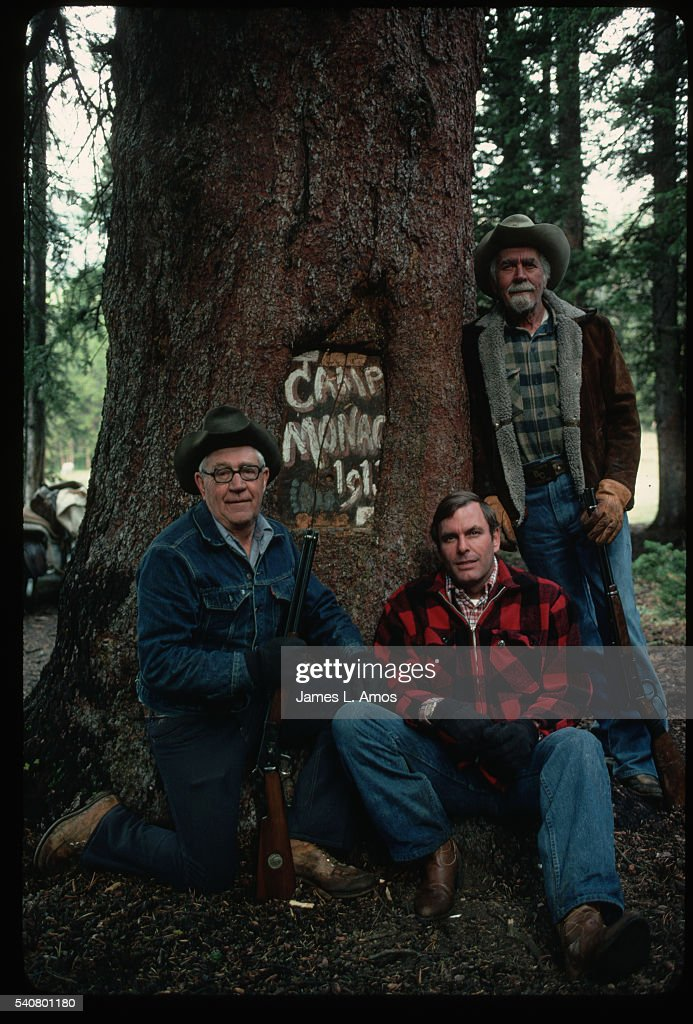 Two grandsons and one great grandson stand beside a sign in the tree trunk for Camp Monaco the hunting camp that Buffalo Bill took Prince Albert of...
