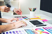 Two Graphic designer drawing on graphics tablet and color palette guide at workplace