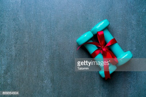 two green dumbbell with red gift bow on a black table background, sport and healthy concep : Stock Photo