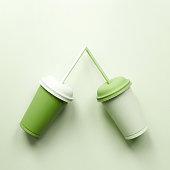 Two plastic cups on green. Greenery love art