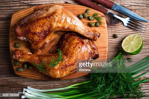 Two grilled chicken legs, green onion, dill and lime on wooden board viewed from above : Stock Photo