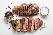 Two grilled marbled beef steaks striploin with spices isolated on white background, top view.