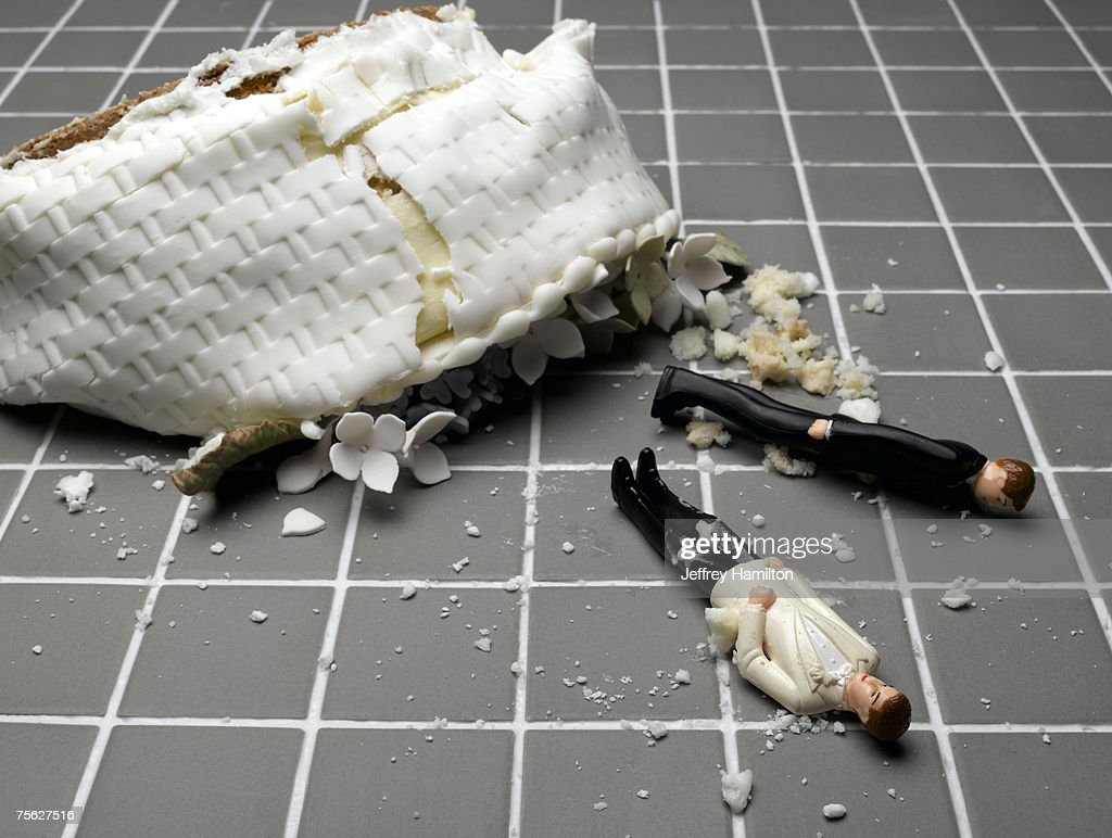 Two groom figurines lying at destroyed wedding cake on tiled floor