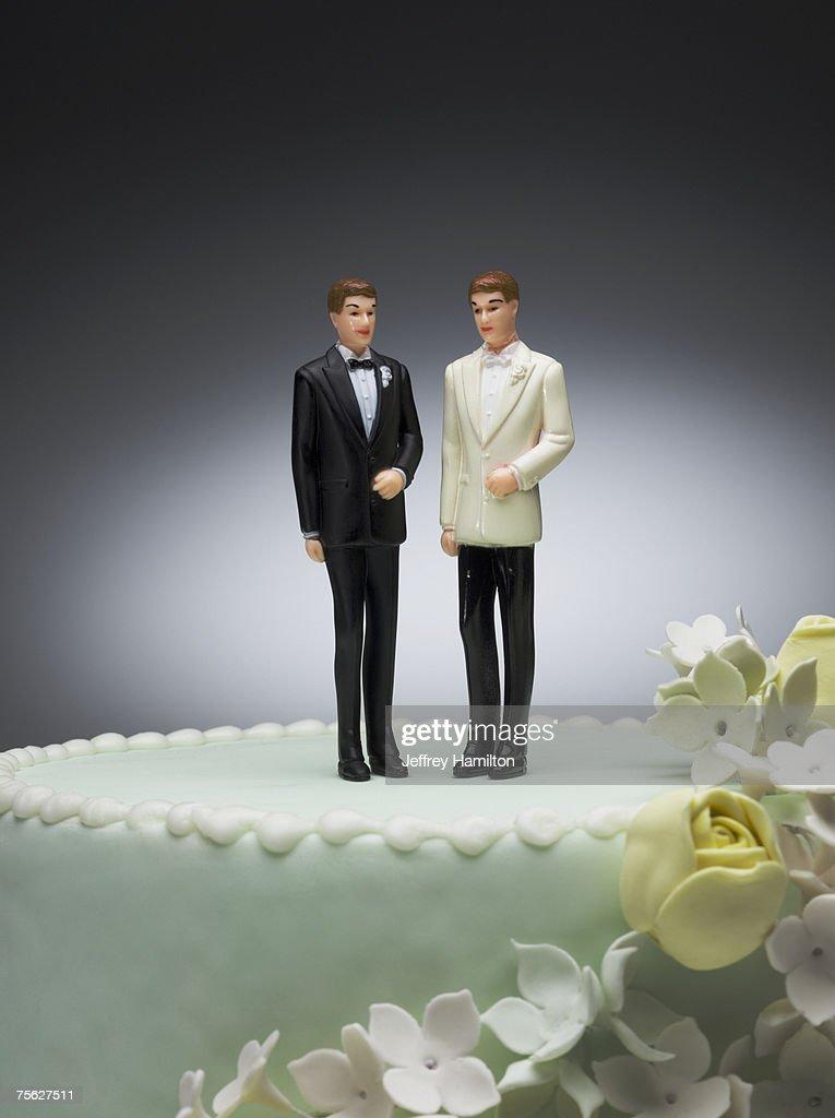 Two groom figurines on top of wedding cake
