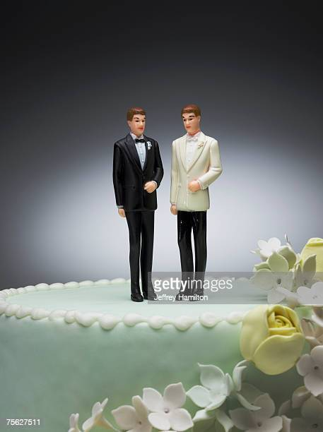 Two groom figurines on top of wedding cake