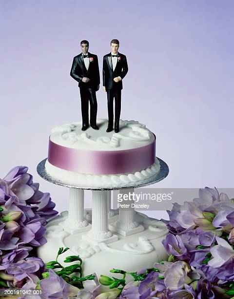Two groom figurines on wedding cake, close-up