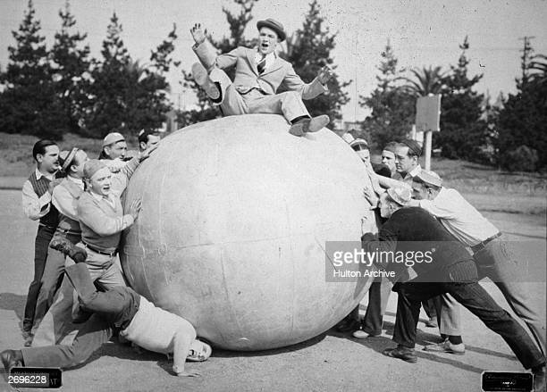 Two groups of men push on opposite sides of a large ball on top of which sits a man who is losing his balance in a still from the silent film 'Going...