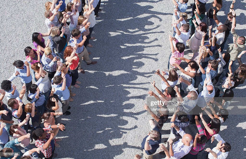 Two groups of people facing one another, arms raised : Stock Photo