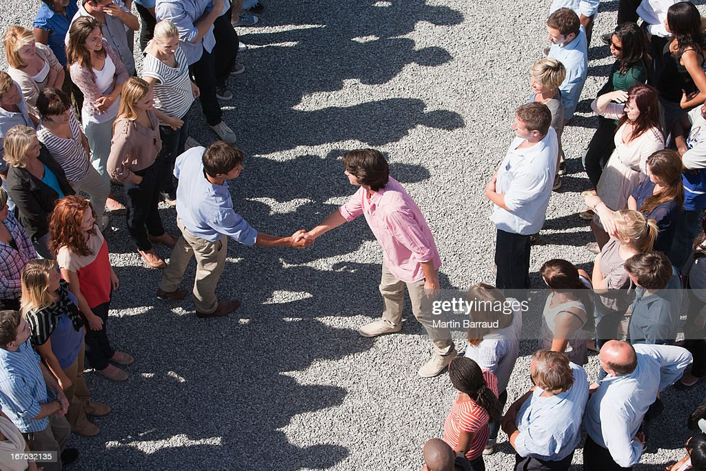 Two groups of people facing one another, two people shaking hands : Stock Photo