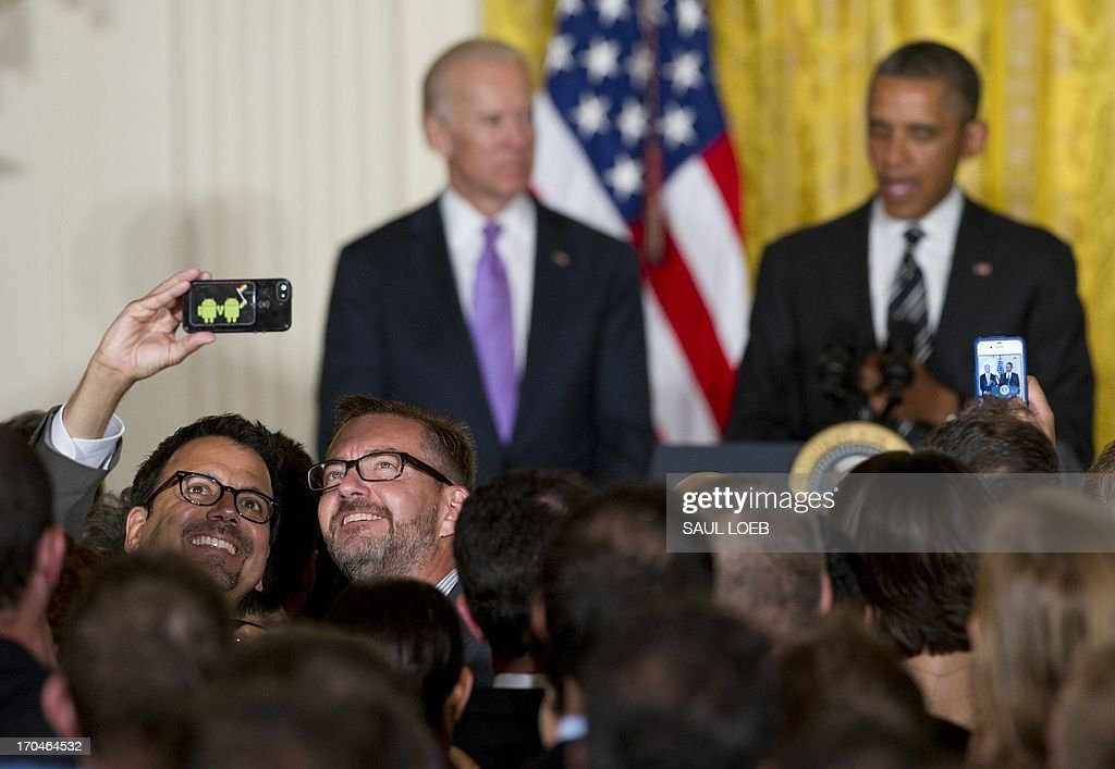 Two guests photograph themselves as US President Barack Obama (R) speaks alongside US Vice President Joe Biden during a LGBT (the lesbian, gay, bisexual, and transgender community) Pride Month celebration in the East Room of the White House in Washington, DC, on June 13, 2013. He praised the courage of people who came out as being LGBT, and those who supported them. From the Senate to the NBA, Obama said, 'We're reaching a turning point.' He said the US has become more loving as a country. AFP PHOTO / Saul LOEB