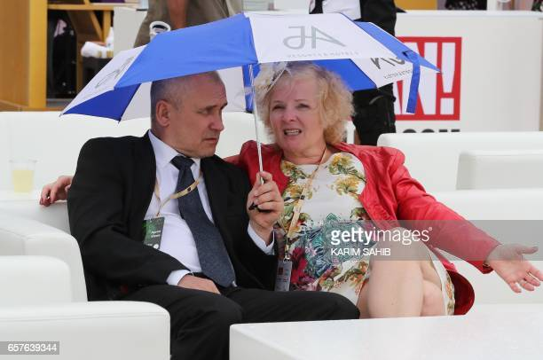 Two guests sit under an umbrella at the Meydan Racecourse as they attend the Dubai World Cup day horse racing event on March 25 2017 in Dubai / AFP...