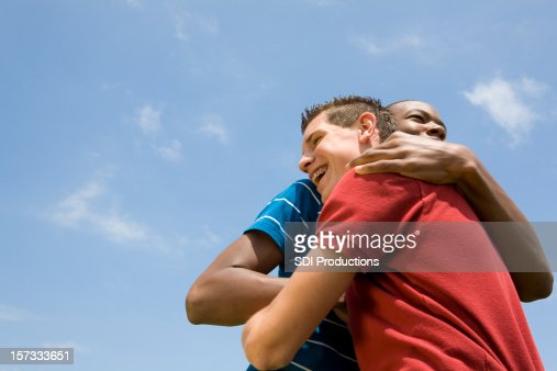 Two Guy Friends Hugging One Another Under The Blue Sky