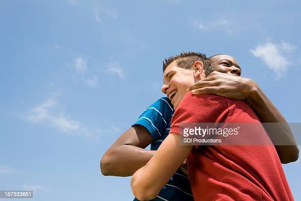 Zwei junge Freunde umarmen einander unter dem blauen Himmel
