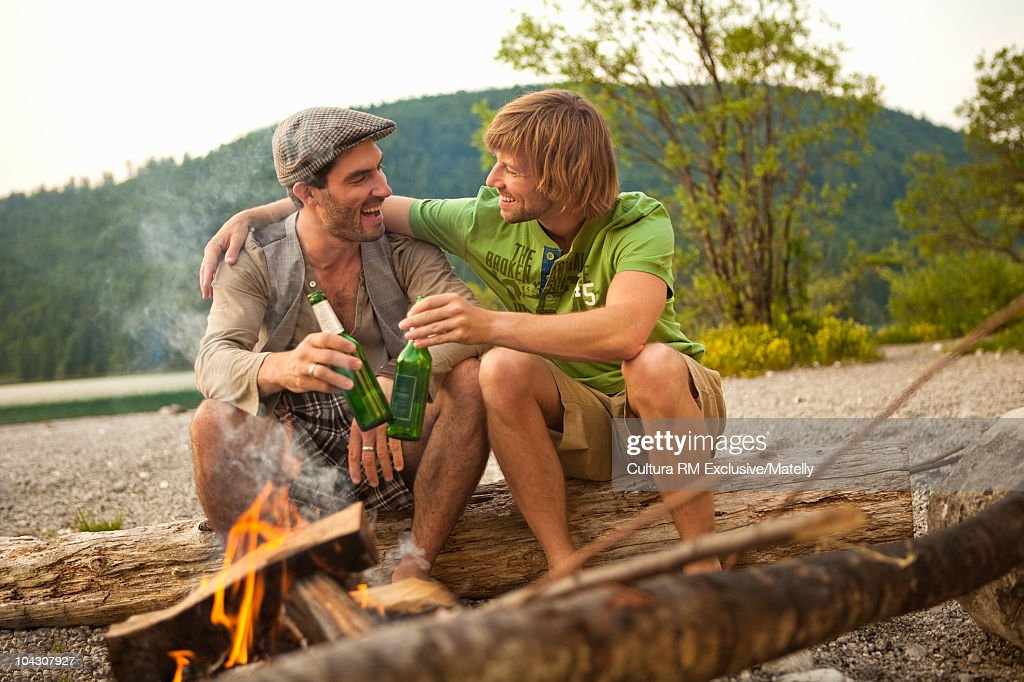Two guys hanging out at a campfire