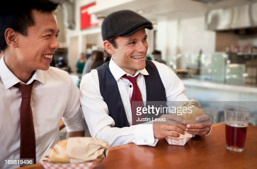 Two guys laughing during lunch in urban restaurant : Stock Photo