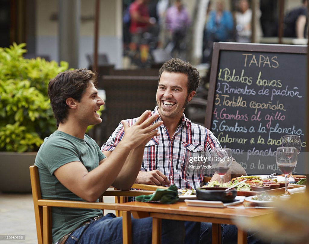 Two guys laughing together at restaurant