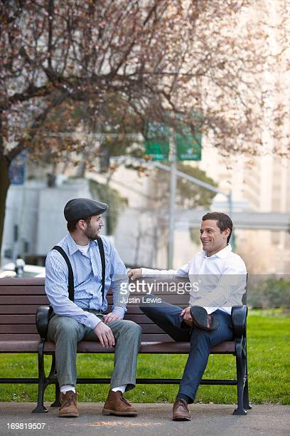 Two guys talking on a city park bench