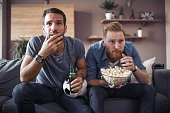 Two guys watching football game,drinking beer and eating popcorn at home.