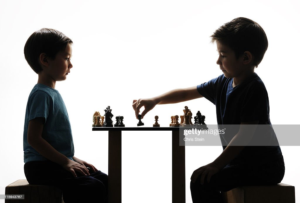 Two Half Asian Brothers playing chess : Stock Photo