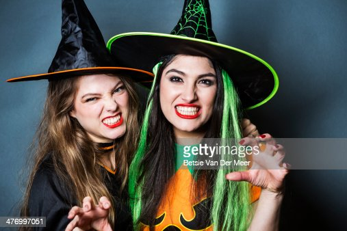 Two halloween witches pulling scary faces.
