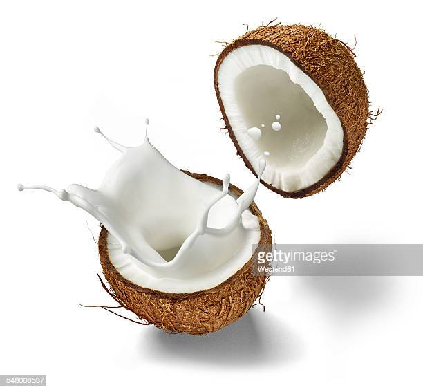 Two halves of a coconut and splashing coconut milk in front of white background