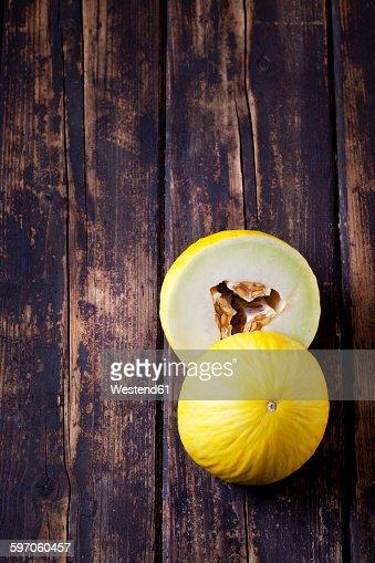 Two halves of honeydew melon on dark wood