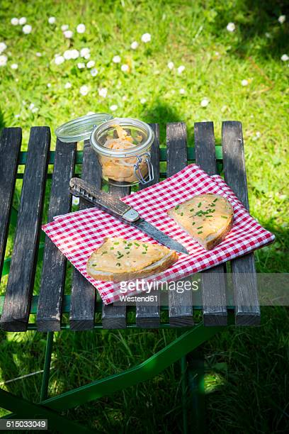 Two halves of slice of bread with obazda sprinkled with chives, cloth, knife and preserving jar on garden table