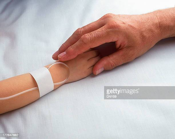 Two hands clasping on hospital bed