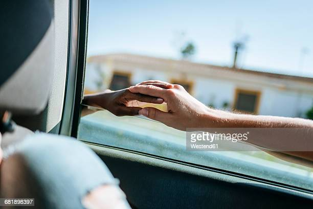 Two hands connected through the window of a car