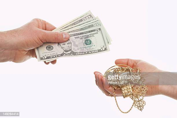 Two hands exchanging money on golden jewelry