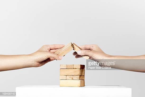 Two hands forming a house shape with wood blocks