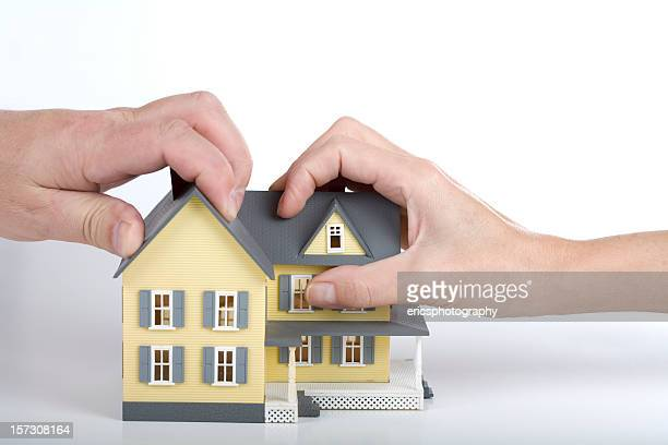 Two hands gripping a yellow model house with grey roof